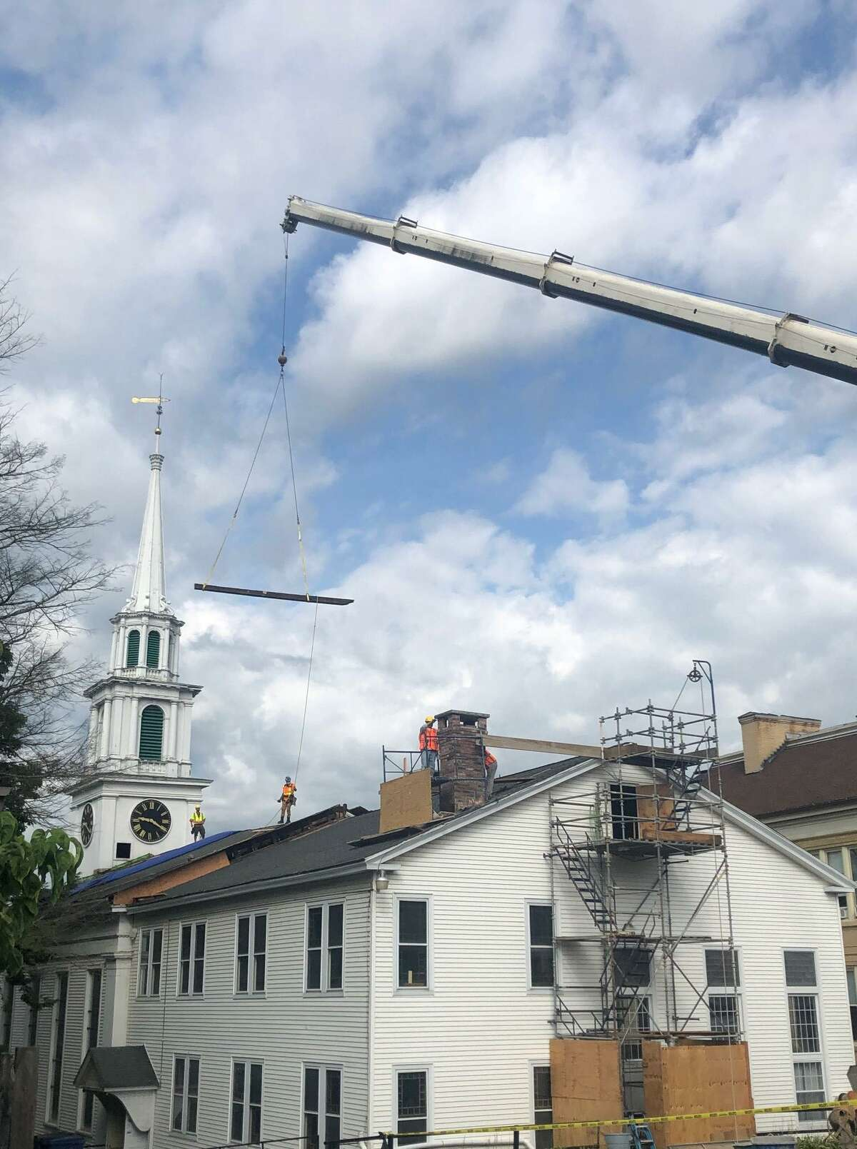 Spectrum/A crowd of First Congregational Church officials and members gathered Aug. 13, 2020 at the on Main Street church in New Milford to view the removal of an historical roof beam from the church building and the installation of a new, steel beam that will stabilize the church building. The roof has been supported by a temporary steel structure since 2013. Above, the first of four pieces of the original structural beam in the church's roof is removed and set in the church parking lot.