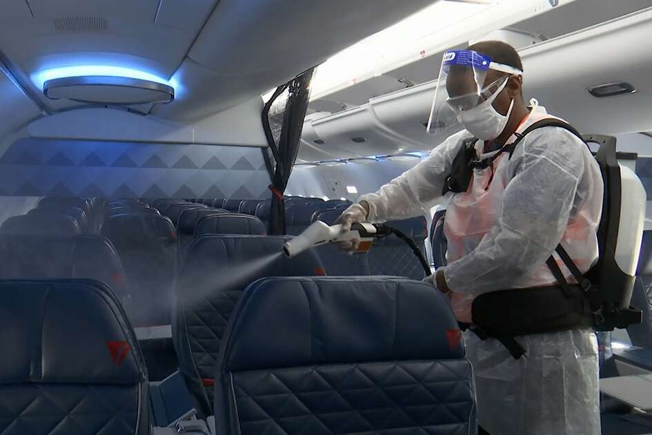 Melaku Gebermariam uses an electrostatic sprayer to disinfect the inside of a Delta Airplane between flights on July 22, at the Ronald Reagan Washington National Airport in Arlington, Va. U.S. airlines have scrambled to reassure travelers that planes are safe. They require passengers to wear face masks and are cleaning cabins more thoroughly, even spraying seats with anti-microbial mist. (AP Photo/Nathan Ellgren)