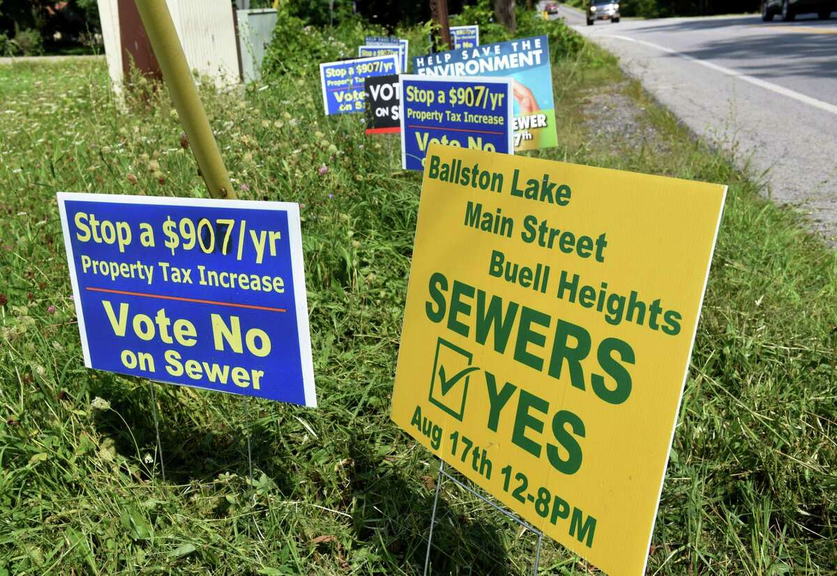 Signs for and against construction of a controversial sewer system planned around the rim of Ballston Lake are placed near the corner of Charlton Road and Goode Street on Monday, Aug. 17, 2020, in Ballston, N.Y. (Will Waldron/Times Union)