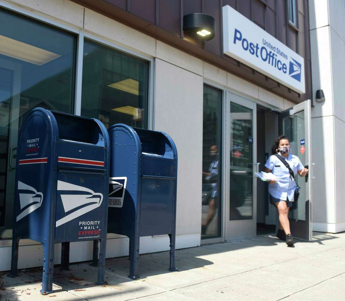 A USPS mail carrier exits the Post Office on Summer Street in Stamford, Conn. Monday, Aug. 17, 2020.