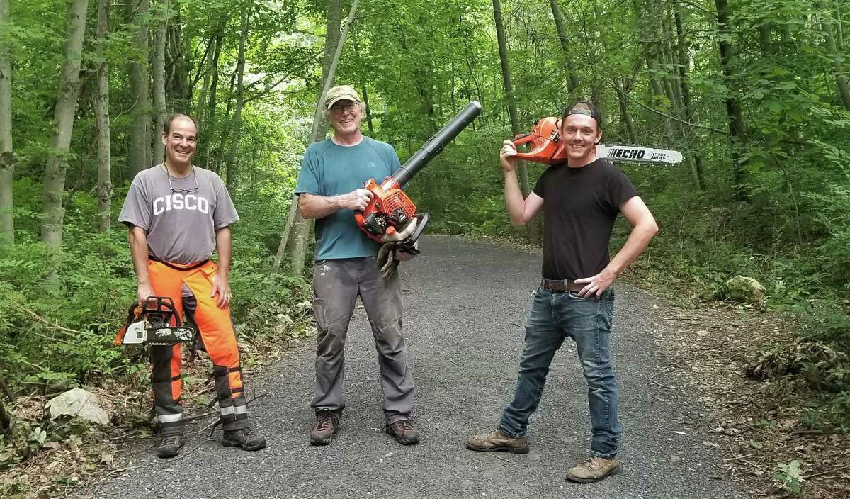 From left, Eric Sesto, Charlie Taney, and Tom Payne are among a dozen volunteers who are cleaning debris left by Tropical Storm Isaias on the 2.2-mile East Wilton Loop of the Norwalk River Valley Trail.