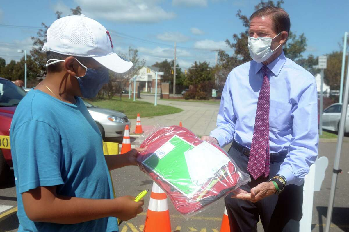 Sen. Richard Blumenthal gives a backpack to eighth grader Sergio Chantes during the