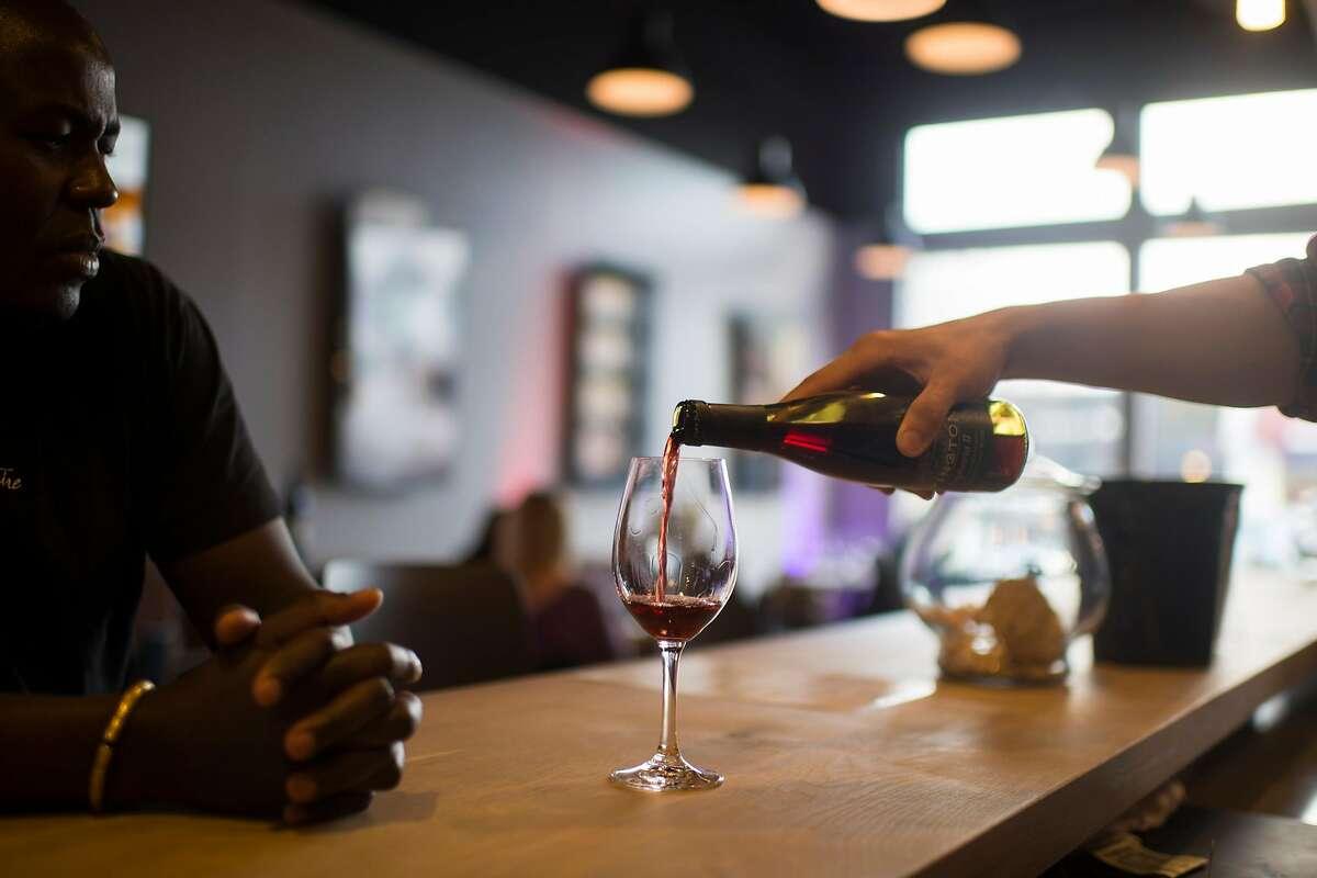 Tasting room associate Theo Haig pours wine at Byington's tasting room in Los Altos.