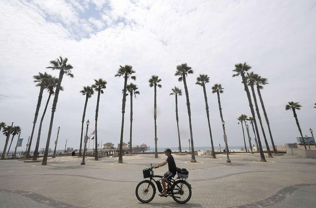 A cyclist rides through the pier plaza in Huntington Beach during last August's California heat wave, which caused rolling power blackouts resulting from high demand.