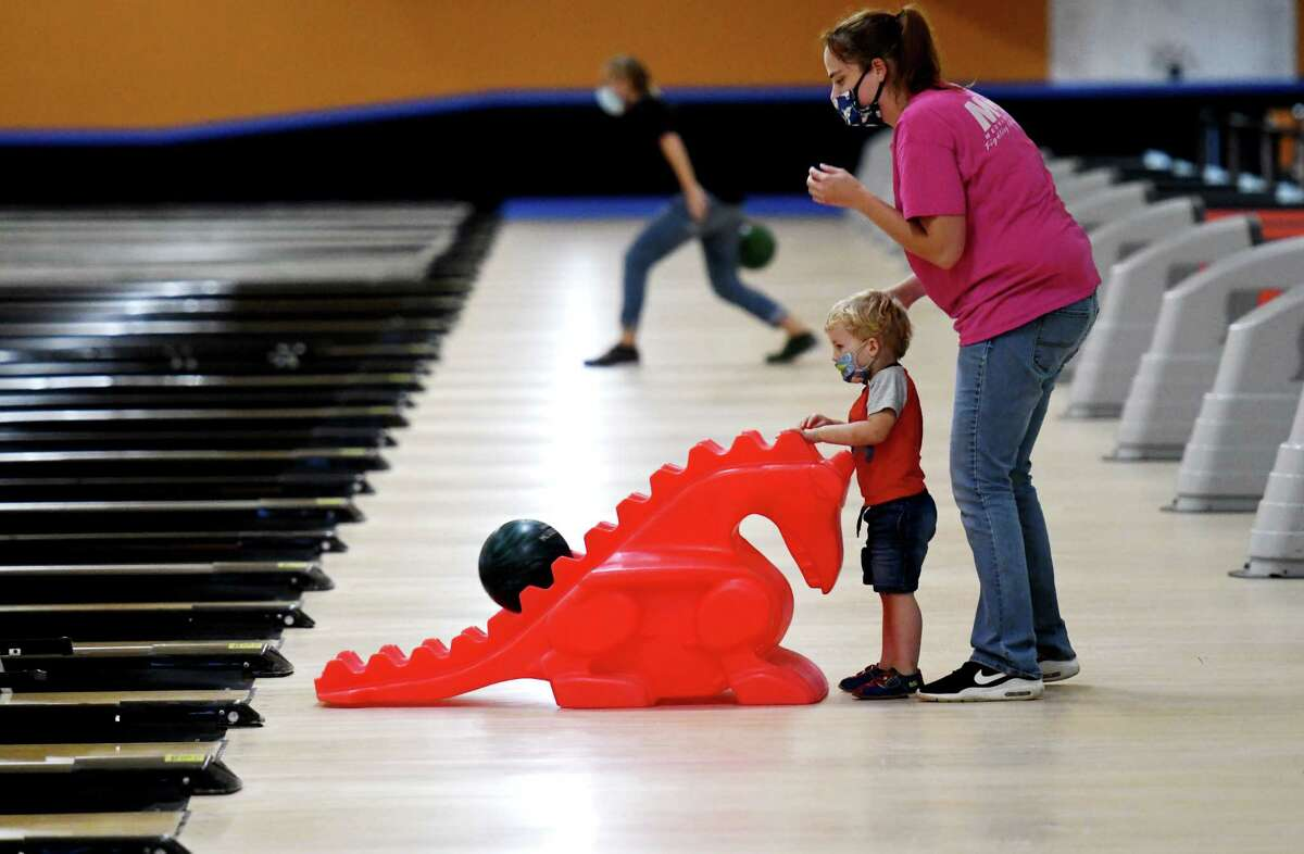 Samual Heil, 2, of Glens Falls gets a helping hand from his mother, Denise, during the first day of reopening for bowling centers under the state's coronavirus guidelines on Monday, Aug. 17, 2020, at Kingpin's Alley in South Glens Falls, N.Y. (Will Waldron/Times Union)
