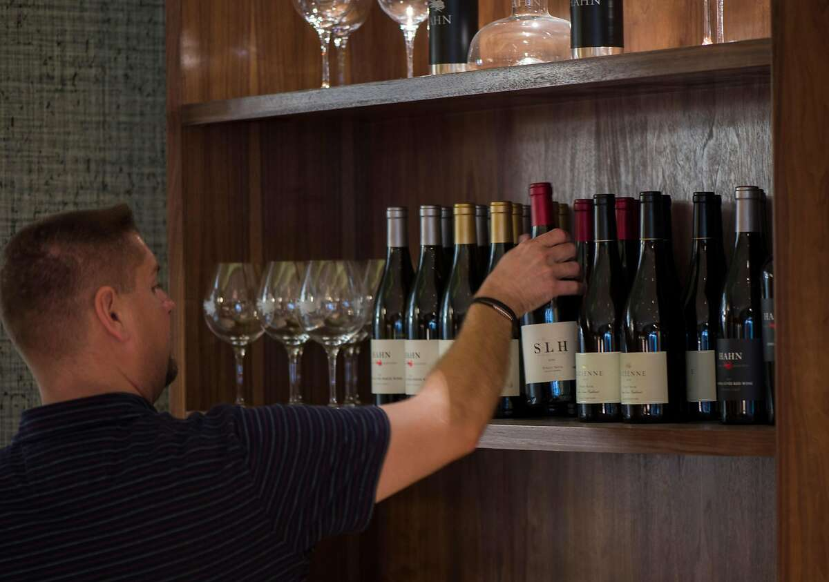Wine club manager Wade Adams organizes bottles at the Hahn Family Winery tasting room in Carmel, Calif.