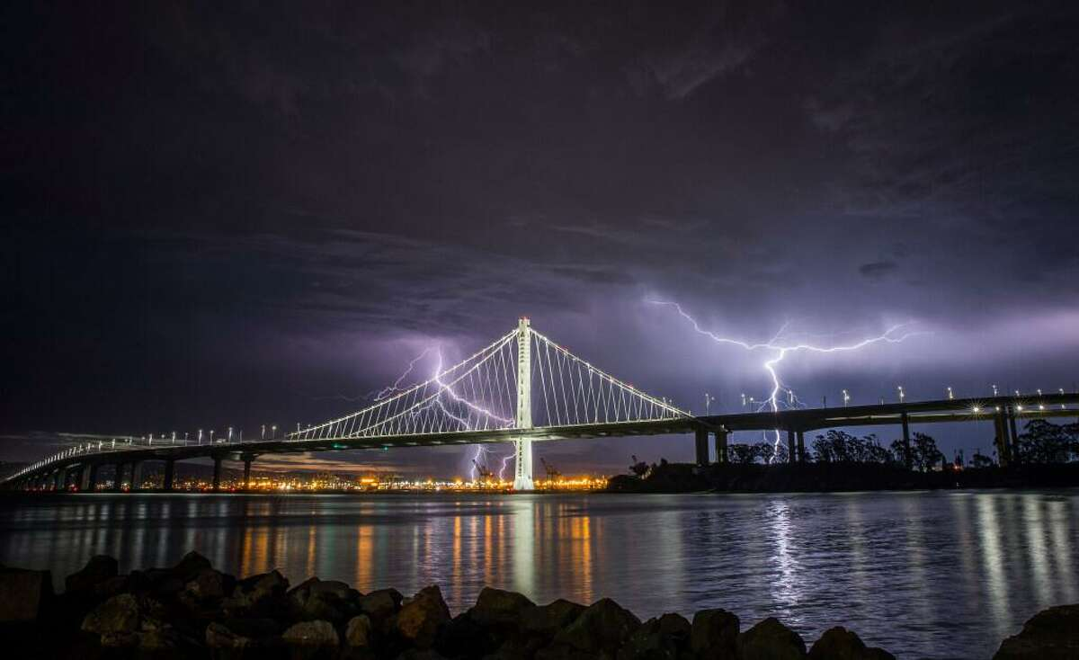 Lightning illuminates the sky over the eastern span of the Bay Bridge as a storm passed through the area on Sunday morning in San Francisco, Calif., on Sunday, August 16, 2020.