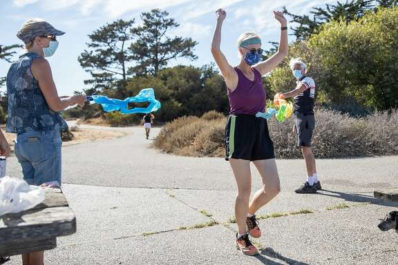 Phyllis Gardner and Gordon Priatko hold a ceremonial finish line while Robin Cohn crosses it at the end of Crosstown Trail in Candlestick Point Park in San Francisco, Calif. Saturday, August 15, 2020. Since October 2018, Cohn has ran every square inch of San Francisco streets, with numerous switch-backs totalling 3,000 miles. She ceremoniously finished her quest Saturday at Candlestick Point Park.