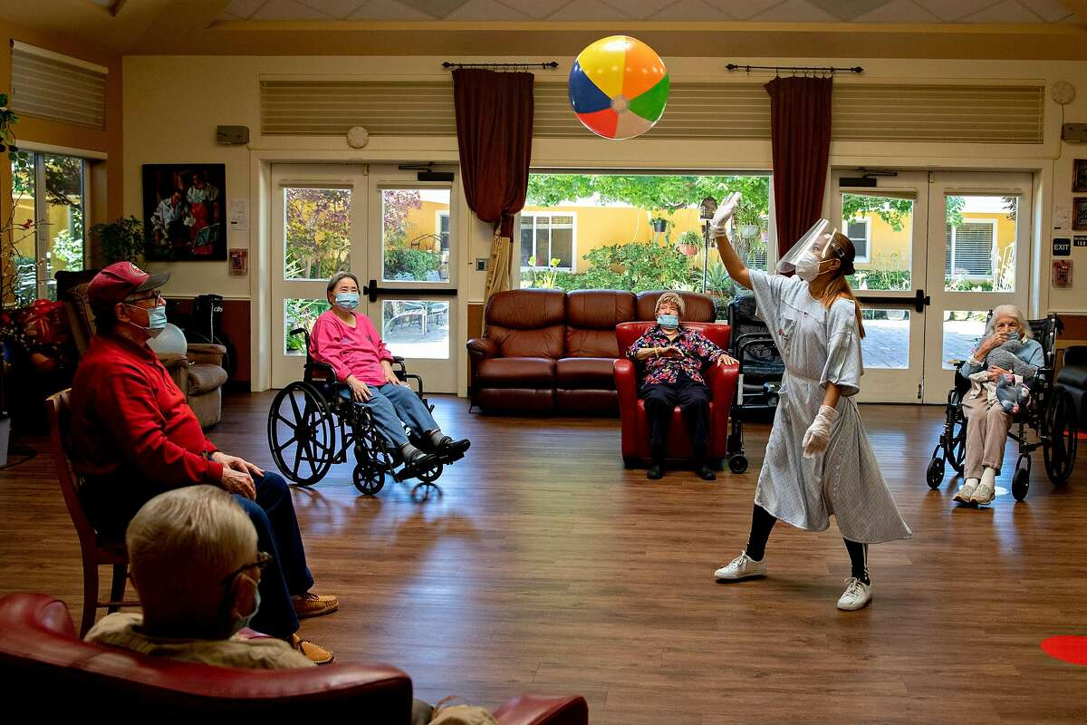 An employee wears full personal protective equipment while leading an exercise with a group of socially distanced residents at Gordon Manor assisted-care facility in Redwood City, Calif. Tuesday, June 30, 2020.