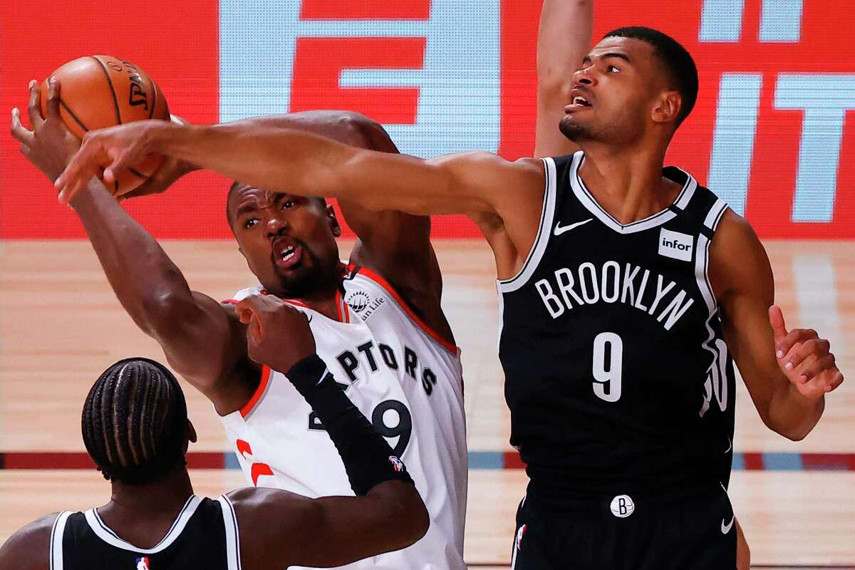 Toronto Raptors' Serge Ibaka, center, grabs a rebound against Brooklyn Nets' Timothe Luwawu-Cabarrot, right, and Caris LeVert, left, during the third quarter of Game 1 of an NBA basketball first-round playoff series, Monday, Aug. 17, 2020, in Lake Buena Vista, Fla. (Kevin C. Cox/Pool Photo via AP)
