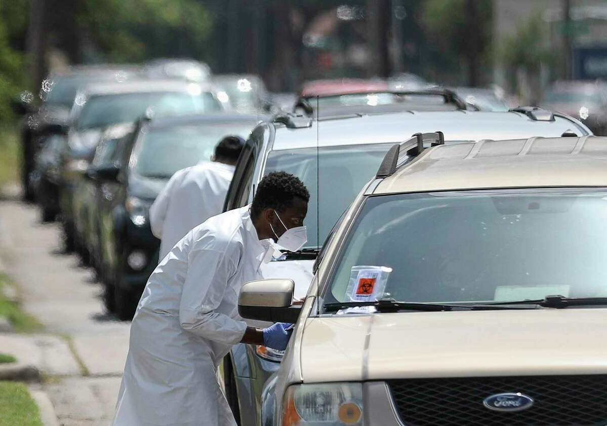 Medical workers talk with people as they wait in their cars along West Tidwell Road for a COVID-19 test Thursday, July 16, 2020, at United Memorial Medical Center in Houston.