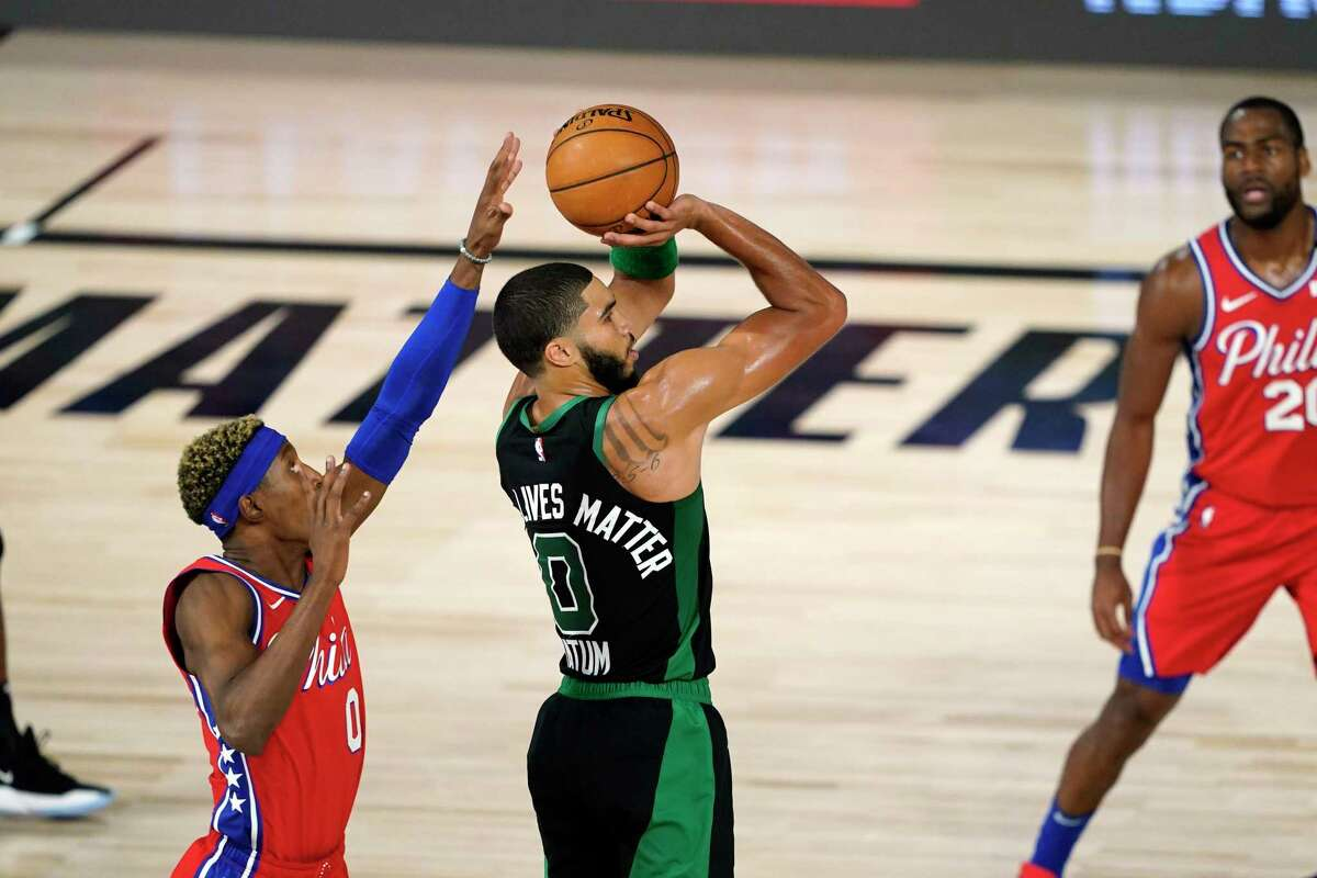 Boston Celtics' Jayson Tatum, center, shoots as Philadelphia 76ers' Josh Richardson, left, defends during the first half of an NBA basketball first round playoff game Monday, Aug. 17, 2020, in Lake Buena Vista, Fla. (AP Photo/Ashley Landis, Pool)