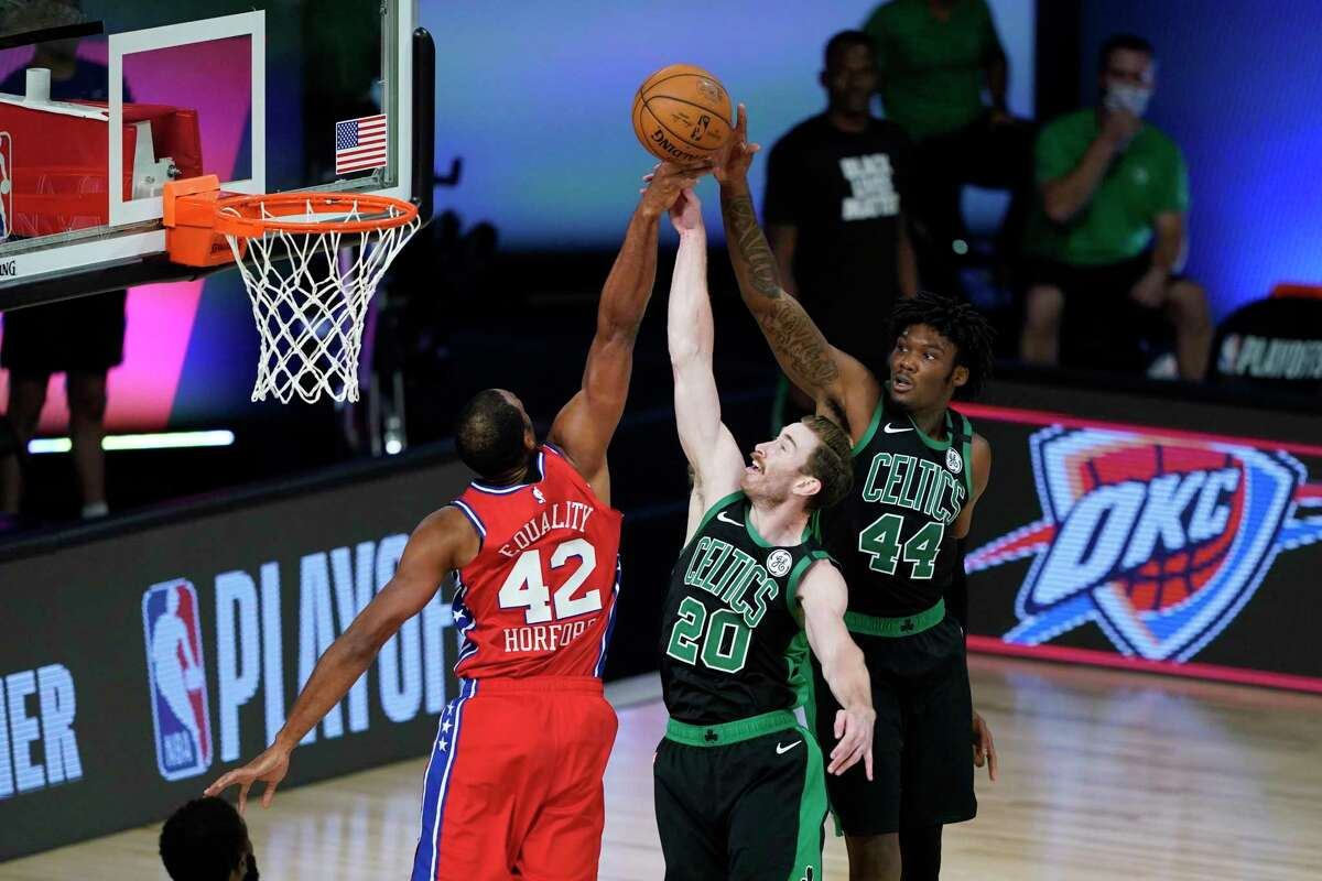 Philadelphia 76ers' Al Horford (42) goes upright for a rebound with Boston Celtics' Gordon Hayward (20) and Robert Williams III (44) during the first half of an NBA basketball first round playoff game Monday, Aug. 17, 2020, in Lake Buena Vista, Fla. (AP Photo/Ashley Landis, Pool)
