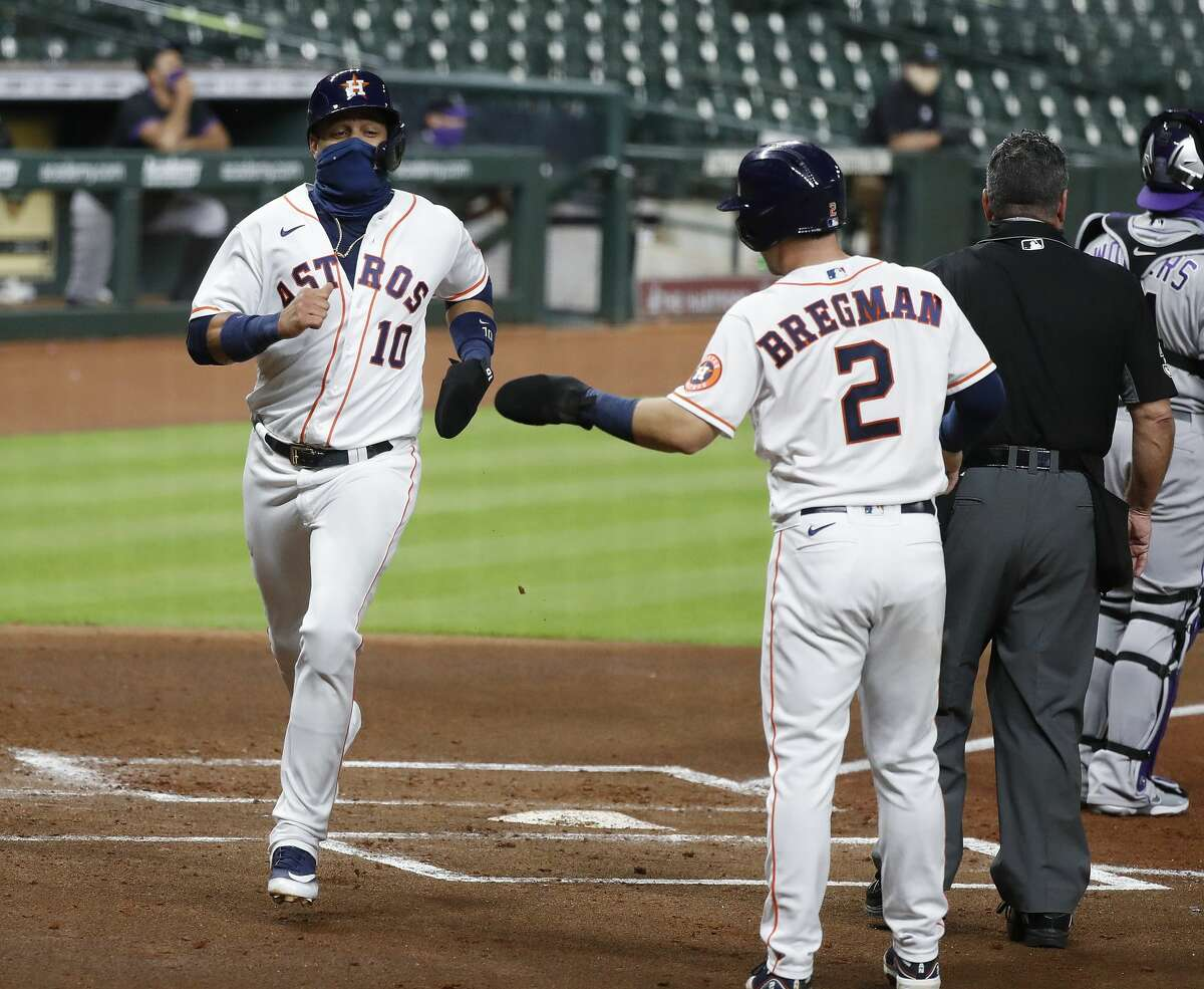 Houston Astros Yuli Gurriel (10) celebrates his run scored with Alex Bregman on Carlos Correa's RBI double during the first inning of an MLB baseball game at Minute Maid Park, Monday, August 16, 2020, in Houston.