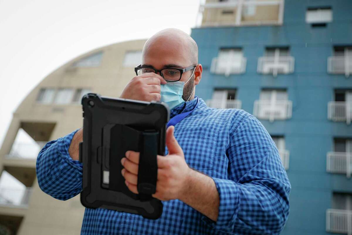 Joseph Ortiz, a contact tracer with New York City's Health + Hospitals battling the coronavirus pandemic, uses his tablet to gather information as he heads to a potential patient's home Thursday, Aug. 6, 2020, in New York. The city has hired more than 3,000 tracers and the city says it's now meeting its goal of reaching about 90% of all newly diagnosed people and completing interviews with 75%. (AP Photo/John Minchillo)