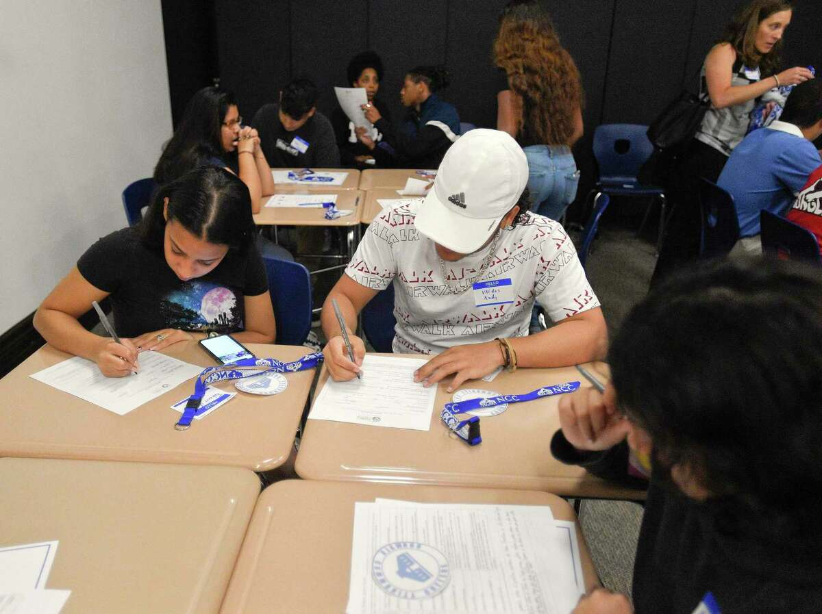 Graduates of Stamford Public Schools fill out a college questionnaire during an event for the