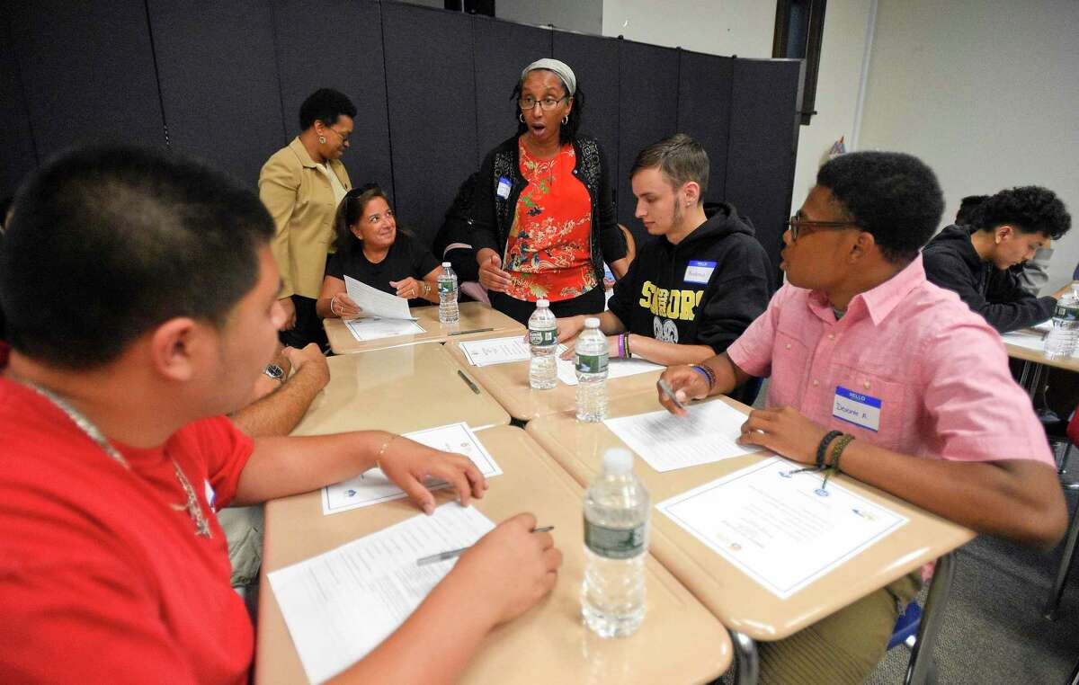High school graduates they fill out a college questionnaire during an event for the