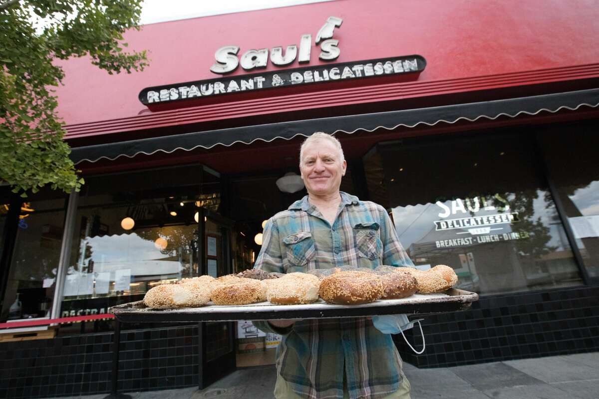 Saul's Restaurant and Delicatessen owner Peter Levitt holds a tray of freshly basked bagels in front of his store in Berkeley, California on Aug. 11, 2020. Saul's will be baking bagels fresh all day for customers.