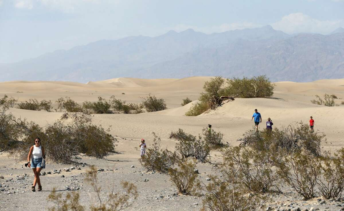 DEATH VALLEY, CALIFORNIA - AUGUST 17: Visitors walk near the Mesquite Flat Sand Dunes on August 17, 2020 in Death Valley National Park, California. The temperature reached 130 degrees at Death Valley National Park on August 16, hitting what may be the hottest temperature recorded on Earth since at least 1913, according to the National Weather Service. Park visitors have been warned, 'Travel prepared to survive.' (Photo by Mario Tama/Getty Images)