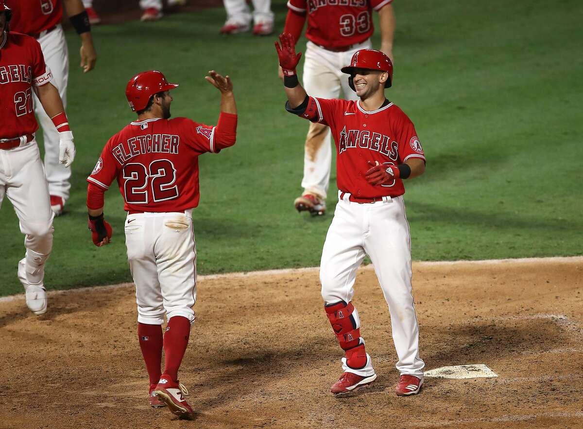 ANAHEIM, CALIFORNIA - AUGUST 17: David Fletcher #22 congratulates Tommy La Stella #9 of the Los Angeles Angels after his game winning two-run homerun during the ninth inning of a game against the San Francisco Giants at Angel Stadium of Anaheim on August 17, 2020 in Anaheim, California. (Photo by Sean M. Haffey/Getty Images)
