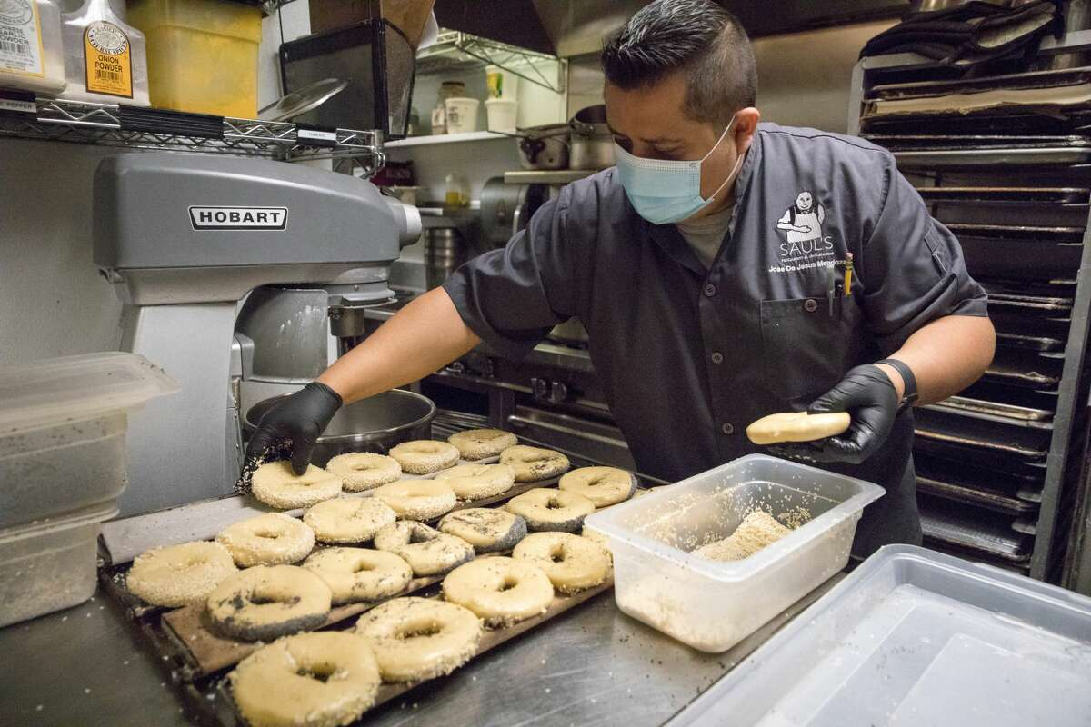 After being boiled, manager Jose De Jesus Mendoza places bagels on a tray to be baked on Saul's Restaurant and Delicatessen in Berkeley, California on Aug. 11, 2020.