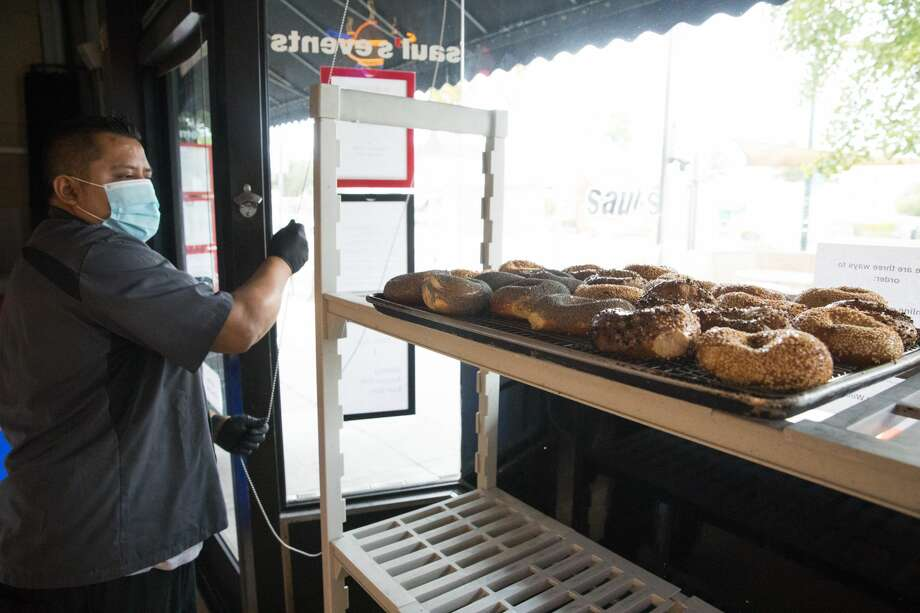 Manager Jose De Jesus Mendoza places freshly baked bagels in the window at Saul's Restaurant and Delicatessen in Berkeley, California on Aug. 11, 2020. Photo: Douglas Zimmerman/SFGATE / SFGATE