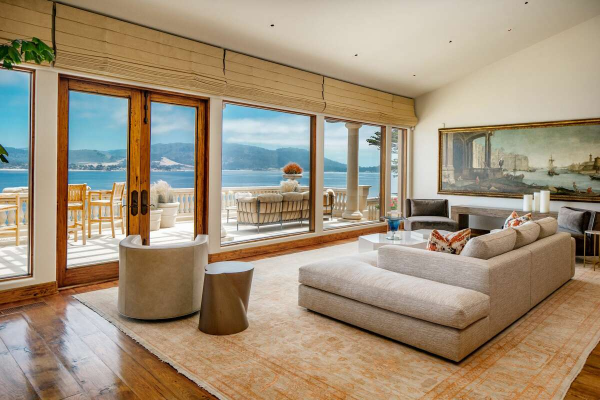 Inside, the home is framed by marble floors, arched ceilings, and walls of glass. The living area looks out and steps out to the sea.