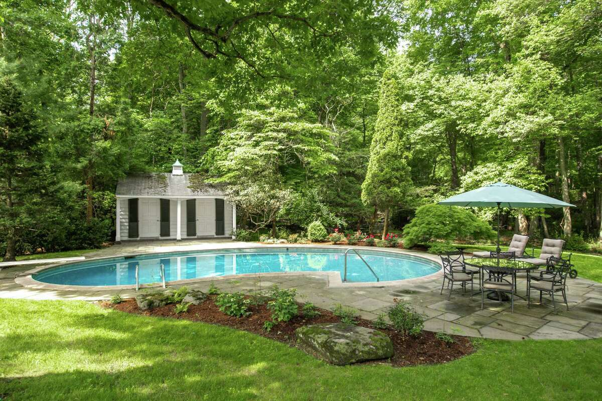 A patio off the rear of the house wraps around the in-ground pool and leads to the pool house. The floor plan affords some more intimate spaces, as well.
