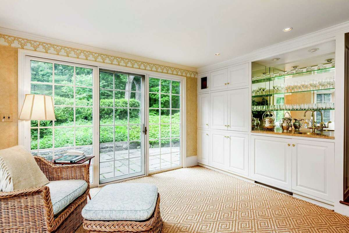 A wet bar is strategically located in the floor plan to facilitate entertaining, whether in the formal public rooms or outside on the terrace. The foyer leads from the front entrance to the public rooms on the main level. A curved,