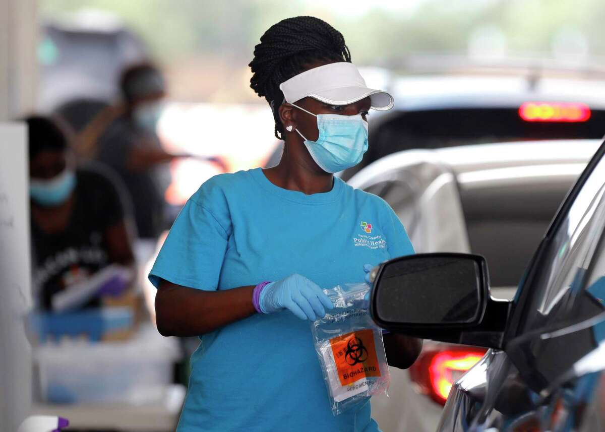 A woman brings testing supplies to a patient for a self-administered coronavirus test at Pridgeon Stadium, Friday, July 31, 2020, in Cypress.