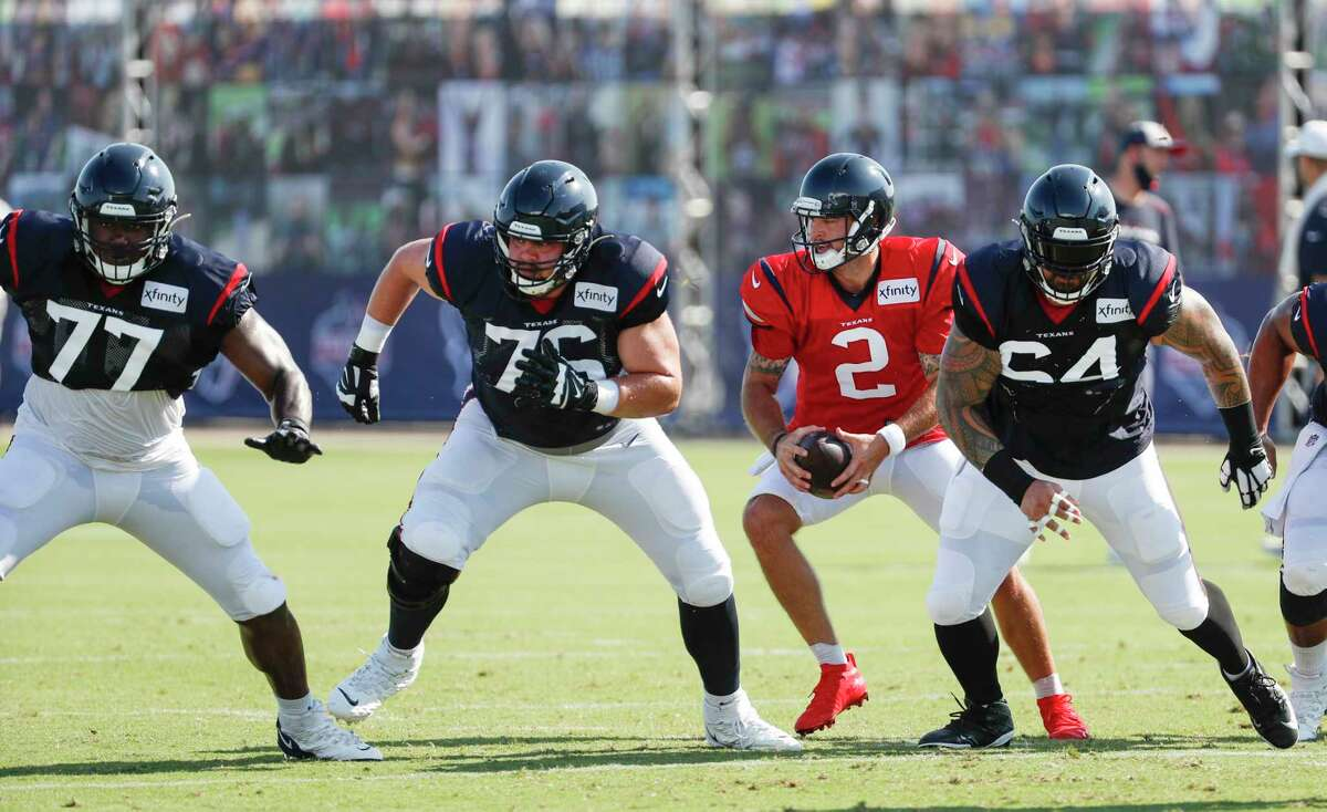 Houston Texans quarterback AJ McCarron (2) runs a play behind Jerald Hawkins (77), Brent Qvale (76) and Senio Kelemete (64) after taking a snap during an NFL training camp football practice Tuesday, Aug. 18, 2020, in Houston.