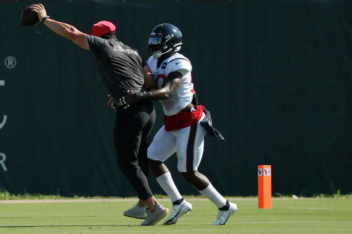 Houston Texans assistant Brian Cushing, left, runs a drill with linebacker Tyrell Adams (50) during an NFL training camp football practice Tuesday, Aug. 18, 2020, in Houston.