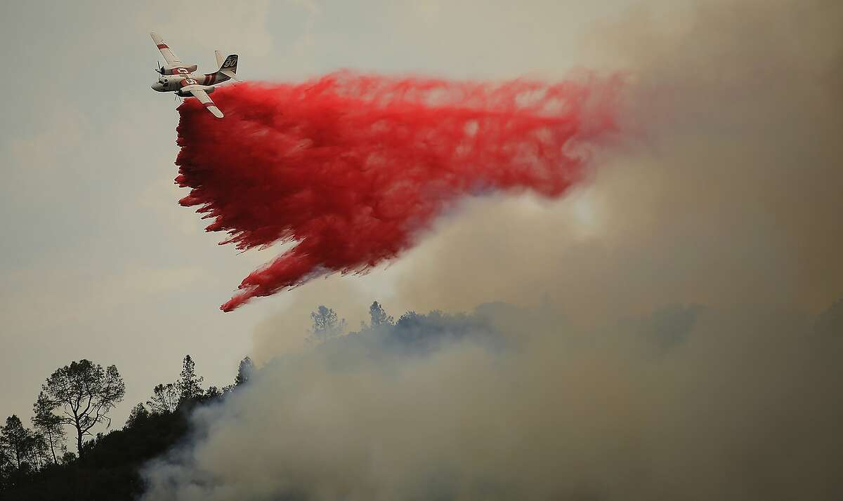 An air tanker makes a drop on a spot fire from the Hennessey fire over lower Chiles Valley Road, Monday, Aug. 17, 2018 in Napa County, California. (Kent Porter/The Press Democrat via AP)