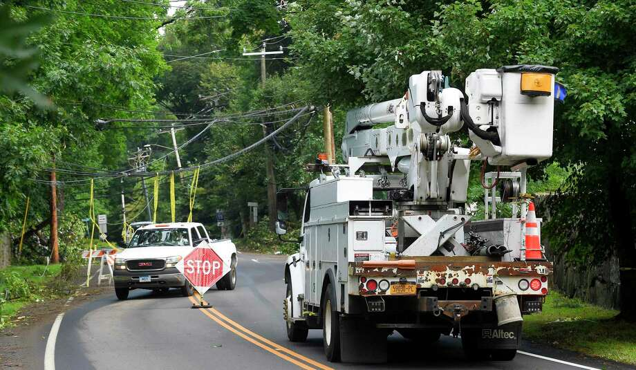 An Eversource truck passes downed utility lines where traffic has been reduced to one lane at the intersection of Lake and North Maple Avenues on Aug. 7, 2020, in Greenwich. Photo: Matthew Brown / Hearst Connecticut Media / Stamford Advocate