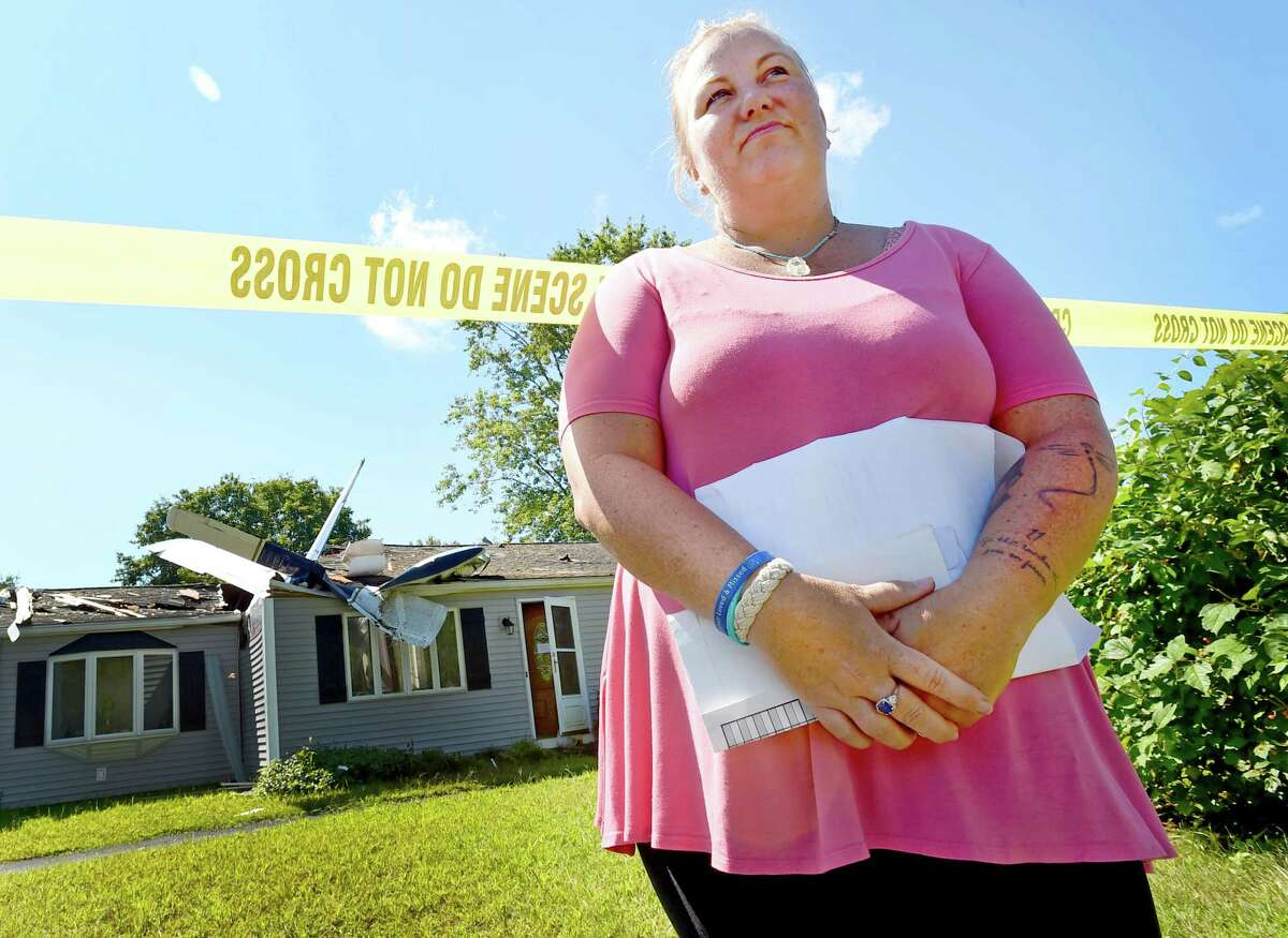 Groton, Connecticut - Tuesday, August 18, 2020: Tammy DelaCruz, the daughter of Kenneth Johnson, 73, stand by her father's house Tuesday where a small plane crashed Monday night at 243 Ring Avenue in Groton where he was sleeping. Johnson was sleeping in house and was able to crawl out the back window of his bedroom uninjured. Police said the airplane's two occupants were able to self-extricate themselves and were transported by ambulance to Lawrence + Memorial Hospital in New London.