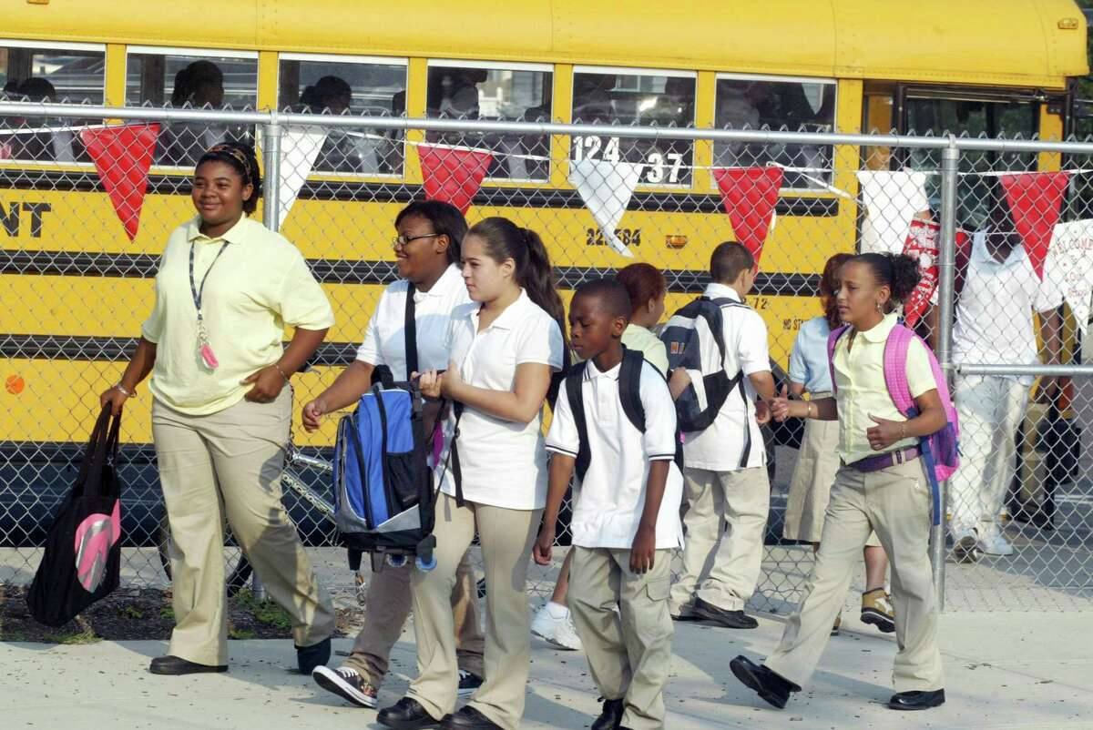 Wearing school uniforms, Waltersville Elementary School students walk to school from their buses in other school years. School uniform rules may be relaxed in favor of concentrating on having students wear masks when school starts this fall.