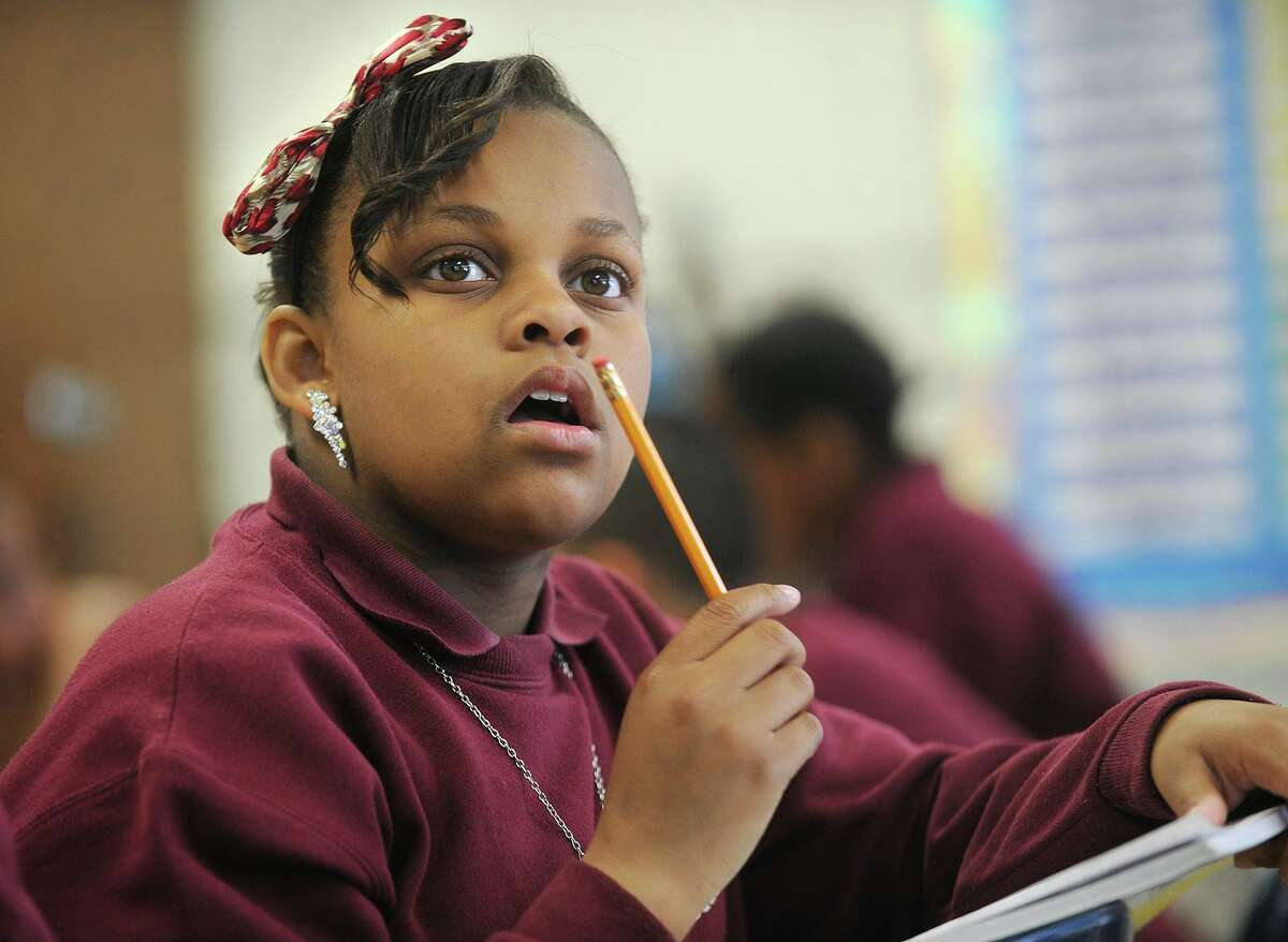 Fifth grader Quadasia Collins wears earrings, a necklace, a pin, and a hair bow to style up her school uniform in Lauren Konigsberg's class at Dunbar School in 2014. School uniform rules may be relaxed in favor of concentrating on having students wear masks when school starts this fall.