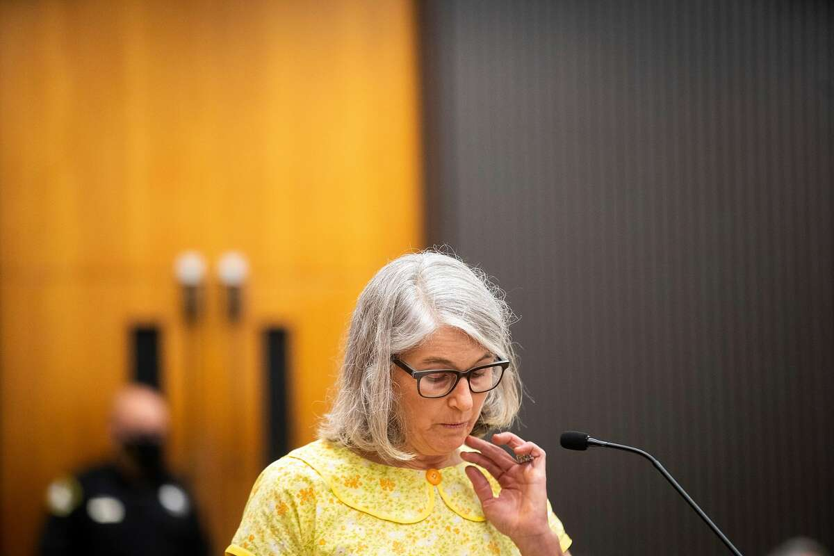"""Peggy Frink reads a statement at the podium as Joseph James DeAngelo is in the court room during the first day of victim impact statements at the Gordon D. Schaber Sacramento County Courthouse on Tuesday, Aug. 18, 2020, in Sacramento. DeAngelo admitted to more than 50 rapes, including some in Santa Clara, Contra Costa and Alameda counties, but the statute of limitations expired on those crimes. DeAngelo, who admitted being the infamous Golden State Killer, listened in to the final statements of his victims and their families, before his sentencing on Friday. Frink, the second victim of the """"East Area Rapist,"""" approached the podium and recalled how she was 15 when DeAngelo broke into her family home and raped her repeatedly while her sister was tied up in another room."""