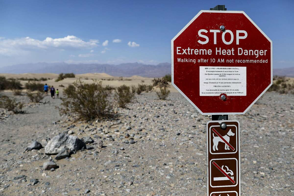 Visitors walk near a sign warning of extreme heat danger on Aug. 17, 2020, in Death Valley National Park, Calif. The temperature reached 130 degrees a day earlier.