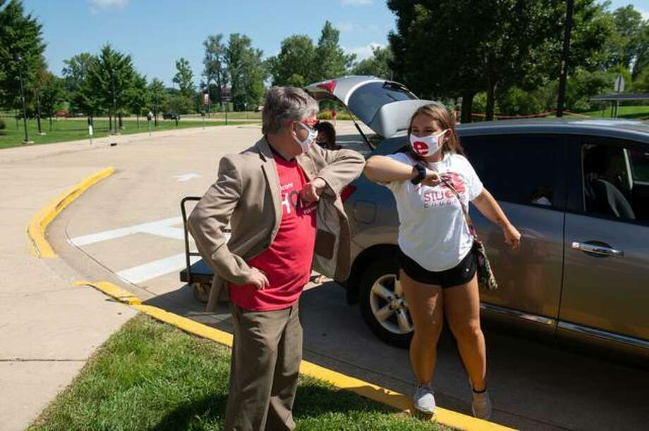 SIUE Chancellor Randy Pembrook bumps elbows with a residence hall student on Tuesday during the first day of student move-in. The process, which normally consists of two separate days, has been switched to five days this year due to the COVID-19 pandemic.