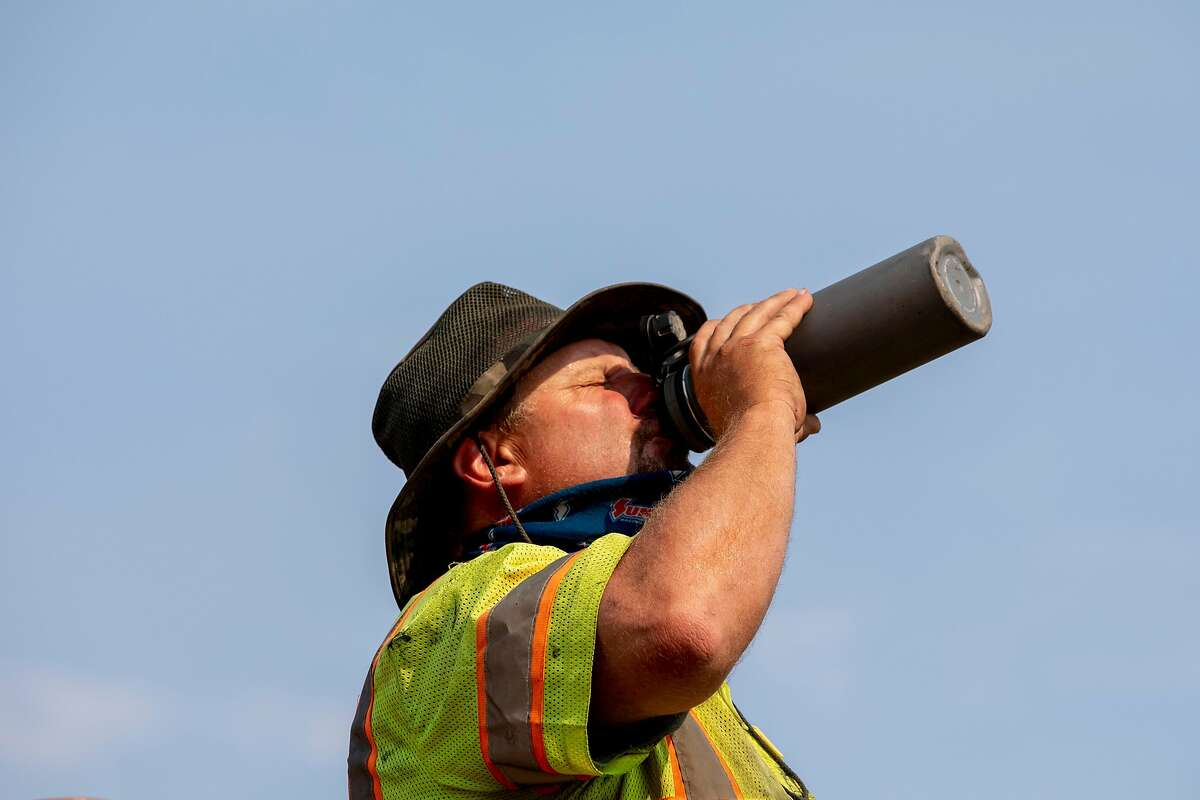 A Contra Costa Public Works maintenance crewmember drinks from a water bottle while completing a chip seal operation on Christie Road in Martinez, Calif. Tuesday, August 18, 2020. City employees and road crews have been working in extreme temperatures during the Bay Area heat wave and stay cool by wearing shaded hats and drinking water consistently.