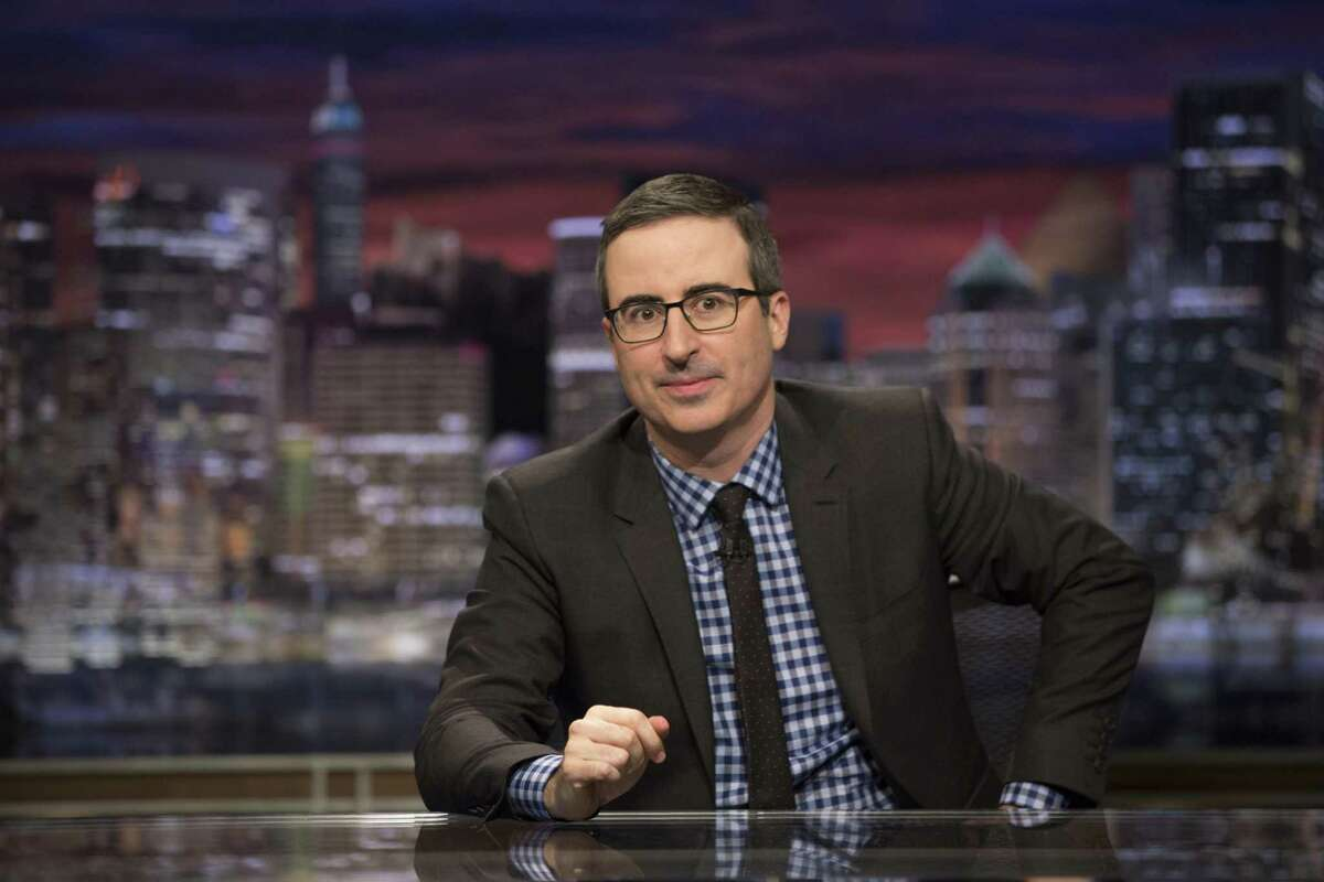 """John Oliver on the set of """"Last Week Tonight With John Oliver."""" Oliver, who first started railing on Danbury in an Aug. 16 episode, was commenting on how the roll call of state delegates in the Democratic National Convention was made virtually in the """"unconventional convention."""" He said the delegates from states and territories """"found novel ways to showcase themselves."""""""