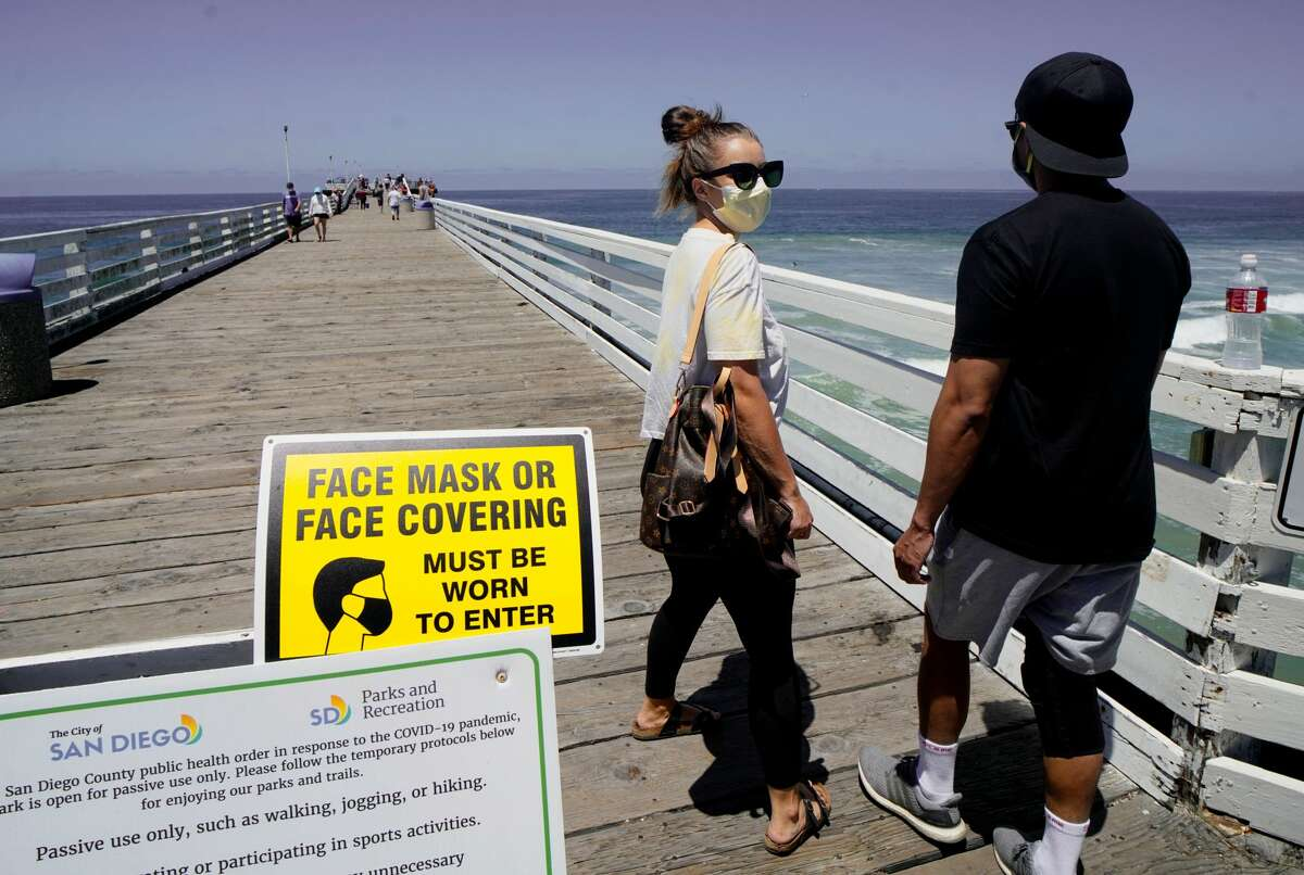 Beachgoers walk out onto the Pacific Beach Pier in San Diego, California on Saturday, July 4, 2020, amid the coronavirus pandemic. - Many beaches have been shut down for the Fourth of July weekend across California due to a resurgence of COVID-19. San Diego area beaches however have remained open.