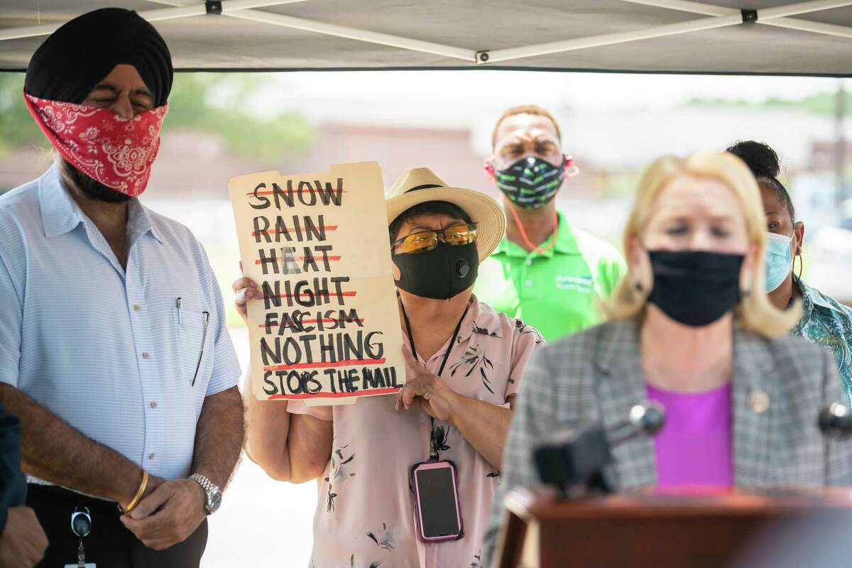 Eva Marron, with the Communications Workers of America, holds a sign as she listens as Congresswoman Sylvia Garcia speaks in front of the United States Postal Service distribution center on Aldine Bender Road on Tuesday, Aug. 18, 2020, in Houston. The Processing and Distribution Center (P&DC) is the largest in the country, and Congresswoman Garcia welcomed constituents and union groups concerned about recent changes impacting mail service.