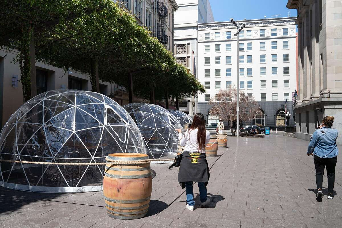 Rene Rodriguez, 47, left, of Pacifica, and Candace Alsalloom, 31, of San Francisco, film on their cellphones while walking past domes outside of Hashiri, a fine dining restaurant, in San Francisco, Calif., on Thursday, August 6, 2020.