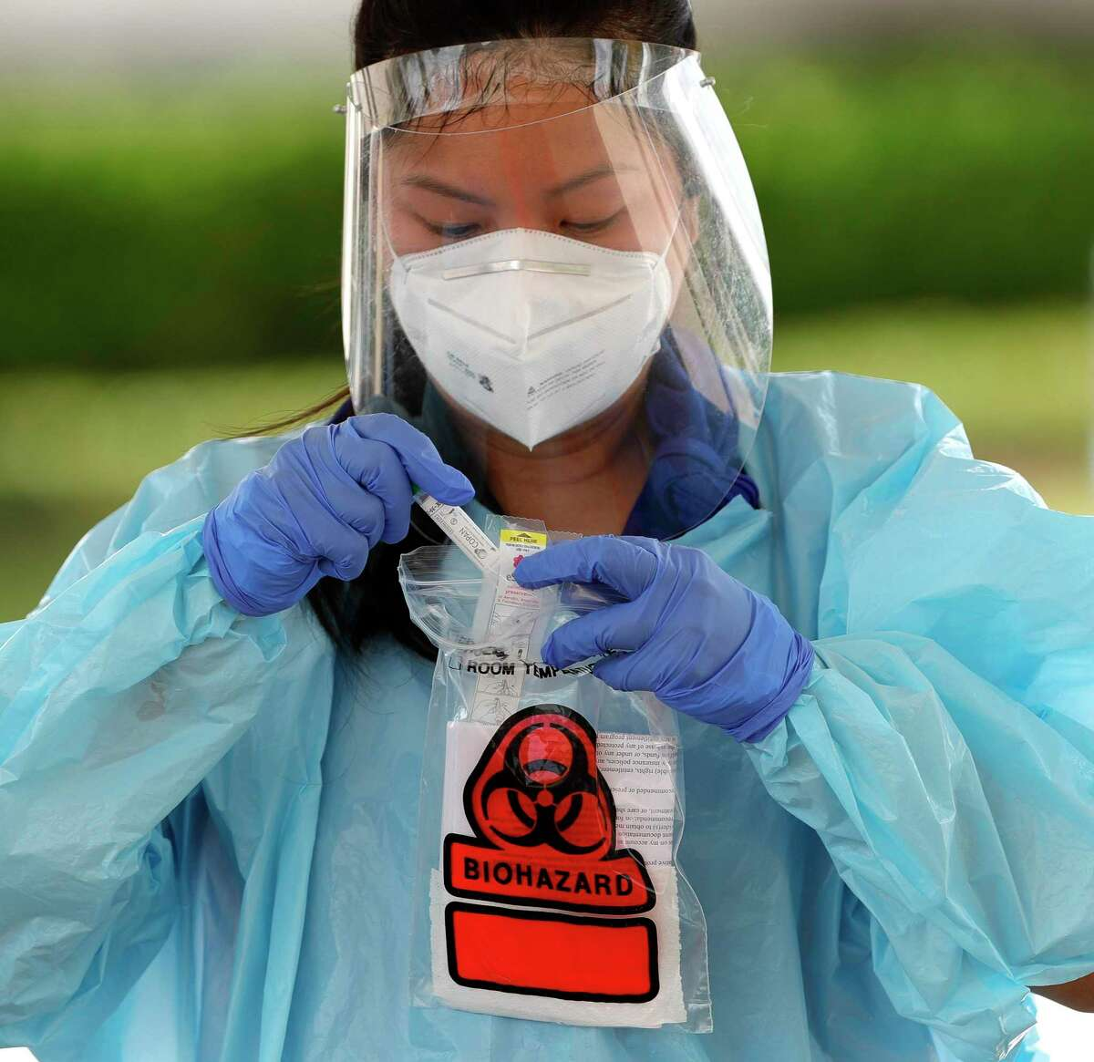 A pharmacist checks a coronavirus test for a patient at a COVID-19 testing site at Bear Branch Sports Fields in The Woodlands. Montgomery County's toll from COVID-19 reached 105 Tuesday, with health officials reporting five more deaths related to the virus.
