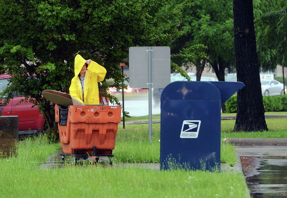 Maria Saldana keeps herself and her mail bin covered against the rain as she makes the day's final pickup at the USPS's Tobe Hahn Station on Thursday afternoon. The National Weather Service has told the area to prepare for three more days of rainy weather, followed by a drier period early next week. Strong to severe storms can be expected from Friday afternoon through Saturday afternoon, and may include large hail and damaging winds. Due to the inclement weather, the Cops and Kids Carnival that was scheduled for Saturday morning on the Event Centre's Great Lawn has been postponed until further notice. Share your local weather photos and event cancellations with the Enterprise by emailing them to LocalNews@BeaumontEnterprise.com. Photo taken Thursday 4/16/15 Jake Daniels/The Enterprise Photo: Jake Daniels / Jake Daniels/The Enterprise / ©2015 The Beaumont Enterprise/Jake Daniels