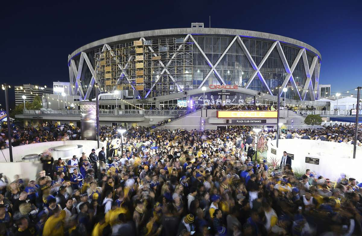FILE - In this June 8, 2018, long exposure file photo, Golden State Warriors fans celebrate outside Oracle Arena in Oakland, Calif. With the distinct possibility of pro sports resuming in empty venues, a recent poll suggests a majority of U.S. fans wouldn't feel safe attending games anyway without a coronavirus vaccine. (AP Photo/Josh Edelson, File)