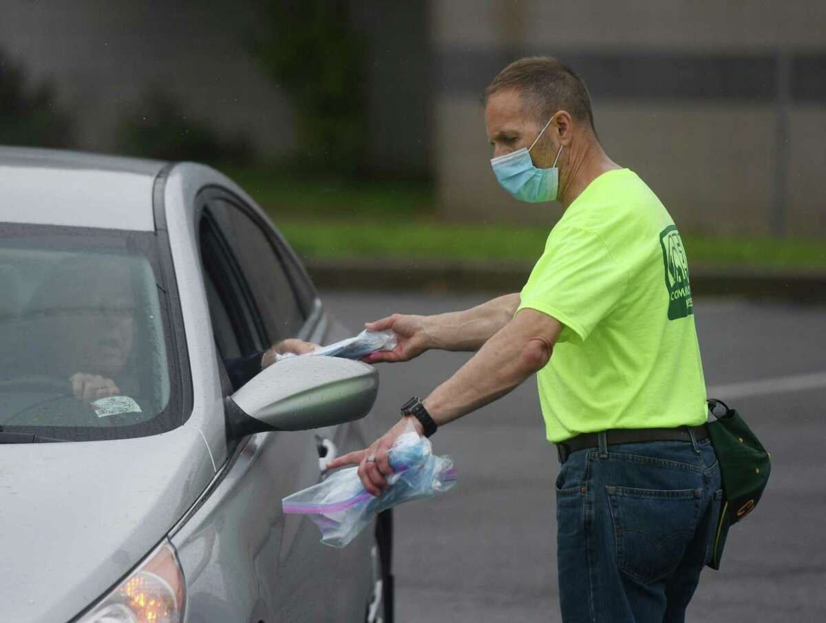 The Stamford Community Emergency Response Team (CERT) distrubutes face masks at Rippowam Middle School in Stamford, Conn. Thursday, Aug. 13, 2020. The group has been handing out about 10,000 masks for free to town residents every Thursday. Mask distribution will continue next Thursday at Rippowam Middle School from 10 a.m. to 2 p.m.