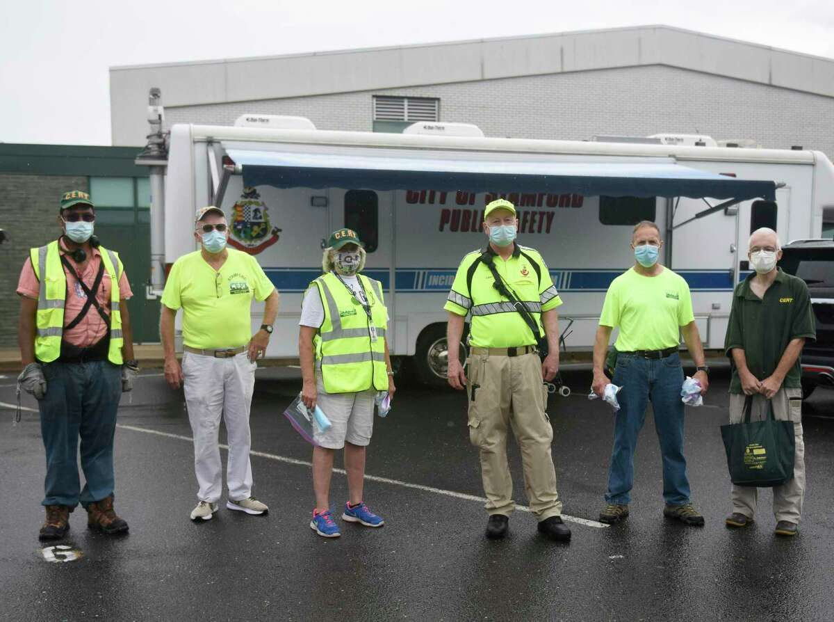 The Stamford Community Emergency Response Team (CERT) poses while distrubuting face masks at Rippowam Middle School in Stamford, Conn. Thursday, Aug. 13, 2020. The group has been handing out about 10,000 masks for free to town residents every Thursday. Mask distribution will continue next Thursday at Rippowam Middle School from 10 a.m. to 2 p.m.